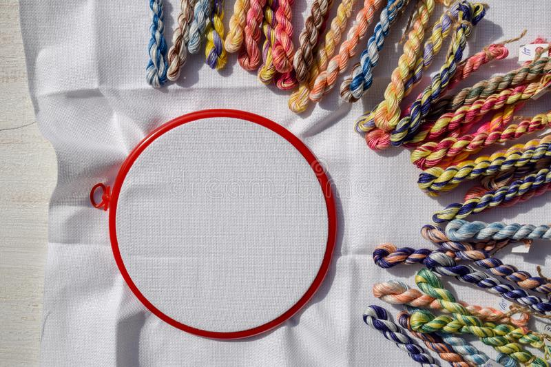 The embroidery hoop with canvas and bright sewing threads stock photos