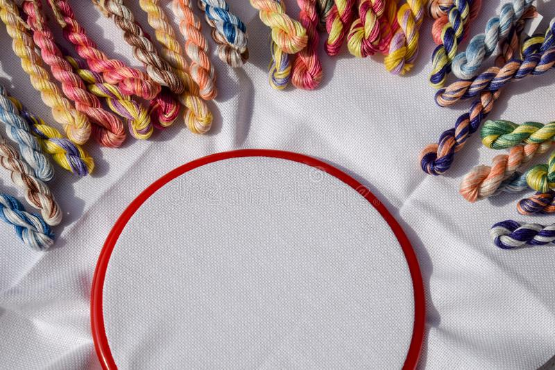 The embroidery hoop with canvas and colored sewing threads stock photos