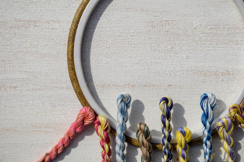 Embroidery hoops for creative art and braided floss threads for embroidery on a light background. Free text space. Creative concept royalty free stock photo