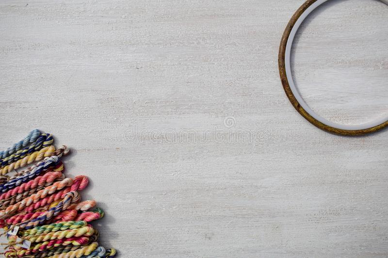 Embroidery hoops for creative art and braided floss threads for embroidery on a light background. Free text space. Creative concept royalty free stock images