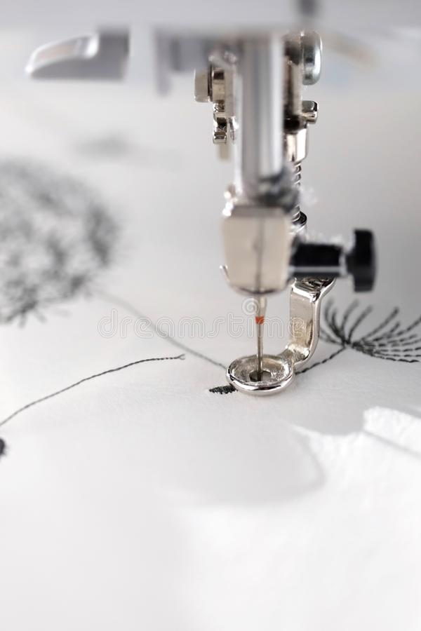 Embroidery with embroidery machine - dandilon on white leatherette - macro detail view in bright sunny light mood. At needle down - portrait orientation royalty free stock image