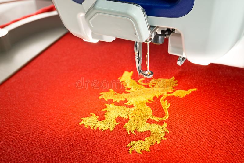 Embroidery machine and gold lion design on red cotton fabric shirt, close up picture. Embroidery machine and finish embroider gold lion design on red cotton stock photography