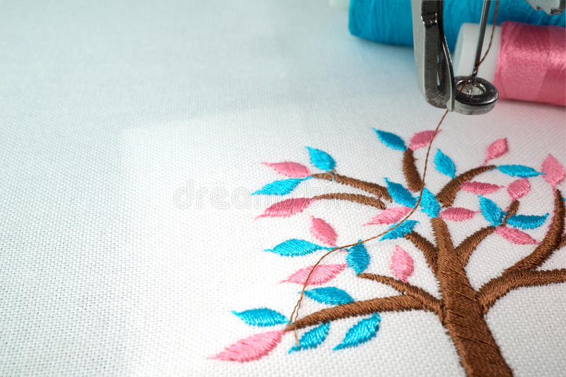Embroidery machine and two threads. Close up macro photo of small brown tree with cyan and pink leafs design on white fabric make with embroidery machine and two royalty free stock photo