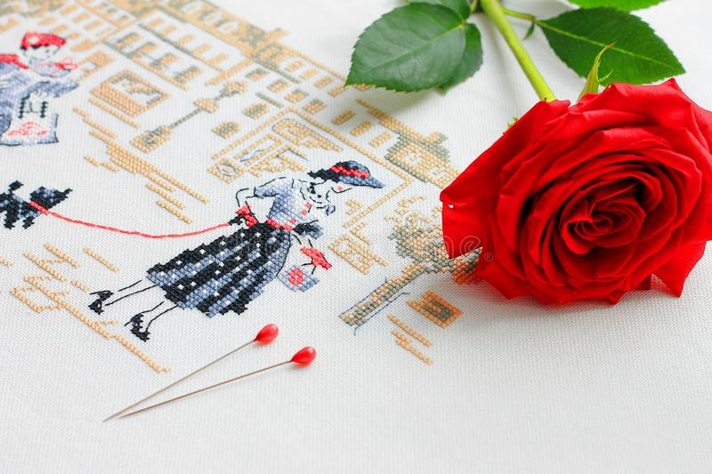 Embroidery with a picture of a young woman on her background red rose and pins for sewing stock photo