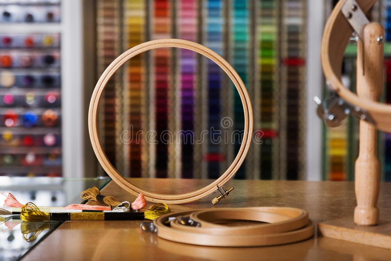 Embroidery ring in shop. Wooden tambour frame standing on desk in sewing store stock photos