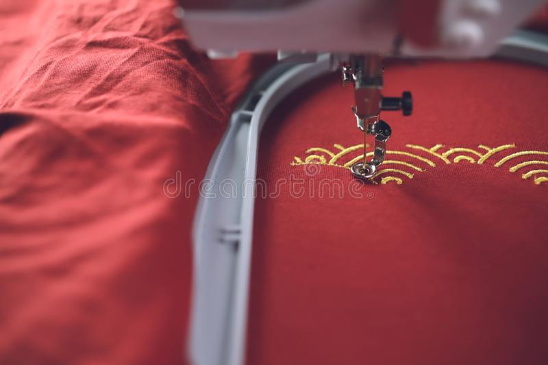 Embroidery of traditional shell pattern with gold on red fabric by modern embroidery machine in progress stock photography