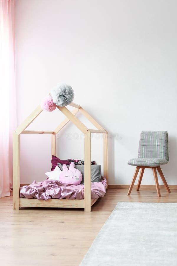 Embroma el dormitorio con la silla gris imagen de archivo