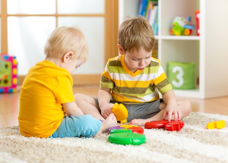 Embroma juegos del niño pequeño con un rompecabezas coloreado multi en cuarto de niños foto de archivo