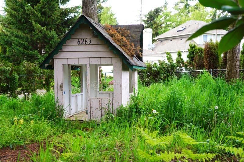 Embroma la casa de madera del juego en la hierba. Patio trasero casero. fotografía de archivo libre de regalías