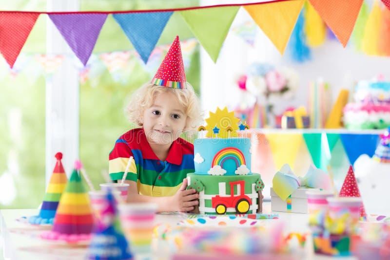 Embroma la fiesta de cumpleaños Niño que sopla hacia fuera la vela de la torta foto de archivo libre de regalías