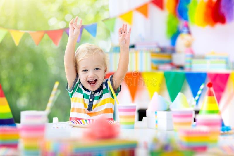 Embroma la fiesta de cumpleaños Niño que sopla hacia fuera la vela de la torta fotos de archivo
