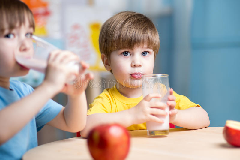 Embroma la leche de consumo de los muchachos en cuarto de niños imágenes de archivo libres de regalías