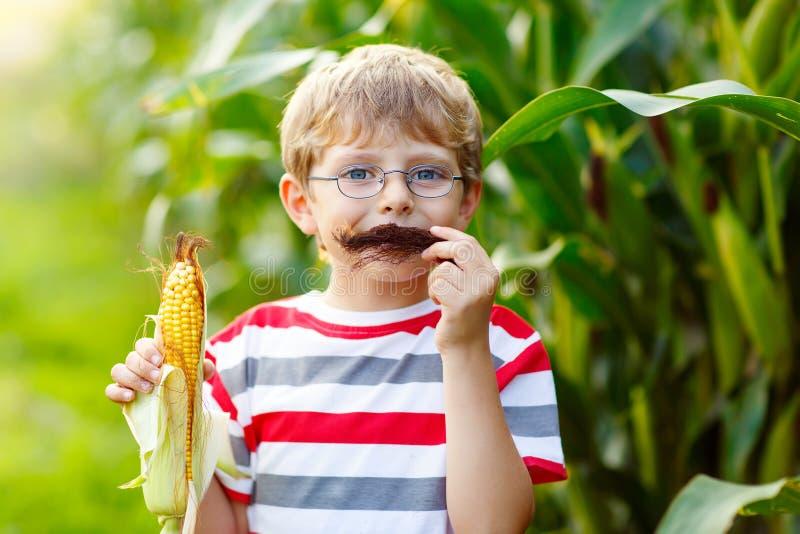Embrome al muchacho con el maíz dulce que se divierte con el bigote fotos de archivo