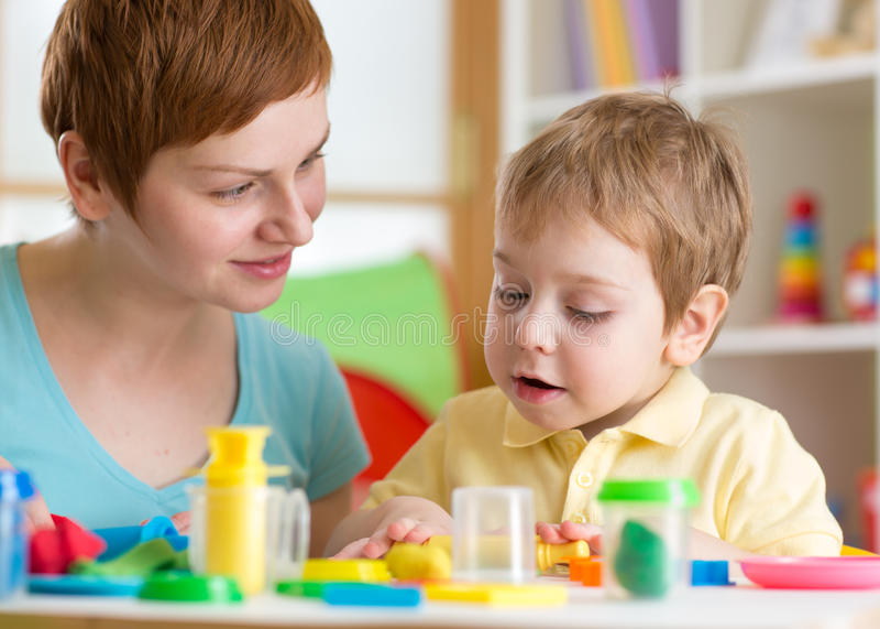Embrome al muchacho con la arcilla del juego del profesor en casa, la guardería, el centro de guardería o el playschool imágenes de archivo libres de regalías