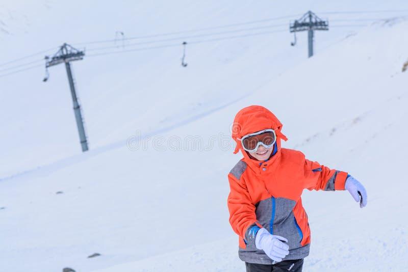 Embrome al muchacho que corre a lo largo del camino con nieve en invierno Laughi feliz foto de archivo libre de regalías