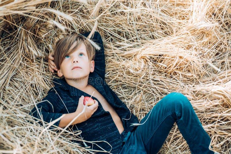 Embrome al muchacho que lleva a cabo la hoja y mentiras de oro en el heno Venta para la colección entera del otoño, descuentos y  fotos de archivo