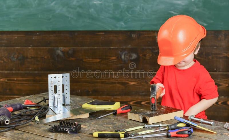 Embrome al muchacho que martilla el clavo en el tablero de madera Niño en jugar lindo del casco demasiado grande como el construc imagen de archivo