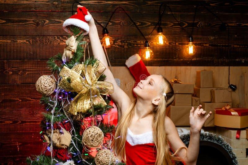 Embrome divertirse cerca del árbol de navidad dentro La mañana antes de Navidad El pequeño adolescente feliz en el sombrero de Pa imagen de archivo libre de regalías