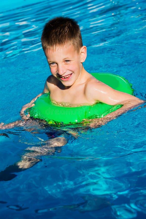 Embrome divertirse en la piscina en el anillo inflable Diversión de las vacaciones de verano imagen de archivo
