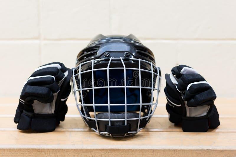 Embrome el engranaje del hockey del ` s en el banco: ennegrezca el casco y los guantes del hockey imagen de archivo libre de regalías
