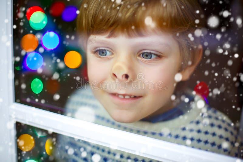 Embrome el muchacho cerca de ventana y la mirada al aire libre en la Navidad imagen de archivo libre de regalías