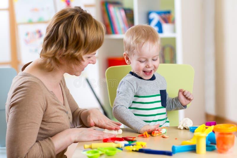 Embrome el muchacho y a la madre que juegan el juguete colorido de la arcilla foto de archivo