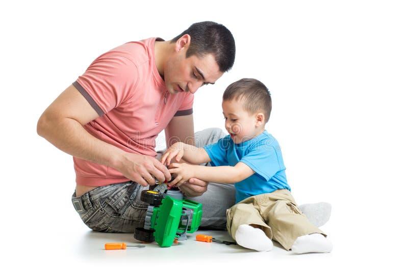 Embrome el muchacho y su coche del juguete de la reparación del padre imagen de archivo