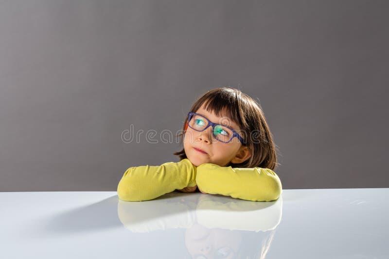 Embrome el pensamiento crítico con el pequeño niño serio y pensamientos dotados imágenes de archivo libres de regalías
