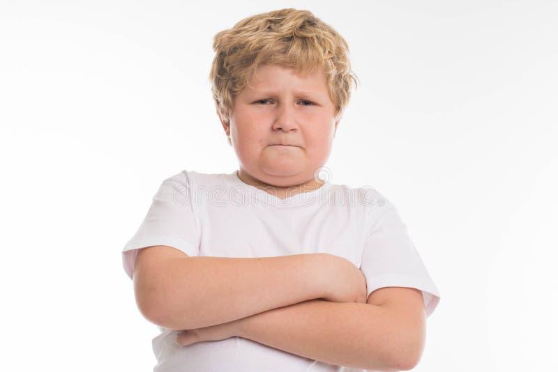 Embrome el retrato enojado del muchacho del estudio del niño en blanco imagen de archivo libre de regalías