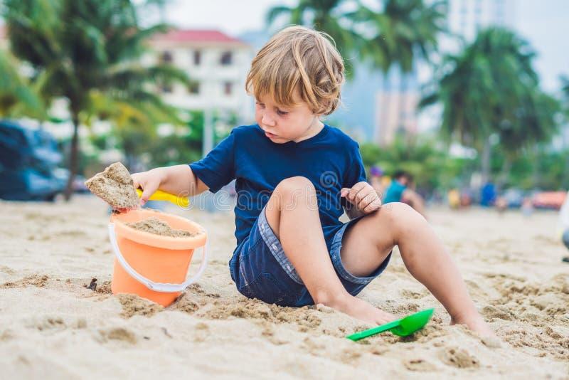 Embrome jugar en la playa con la pala del ` s de los niños y un cubo foto de archivo