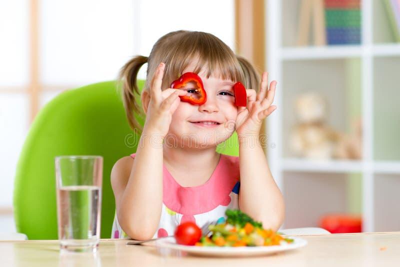 Embrome a la muchacha que se divierte con las verduras de la comida adentro foto de archivo