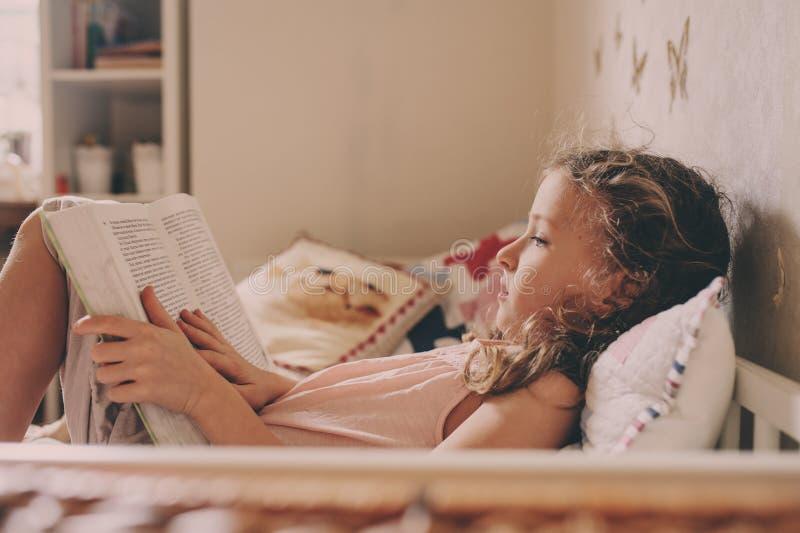 Embrome a la muchacha que se sienta en el libro de la cama y de lectura en su sitio Fin de semana acogedor en casa imagen de archivo