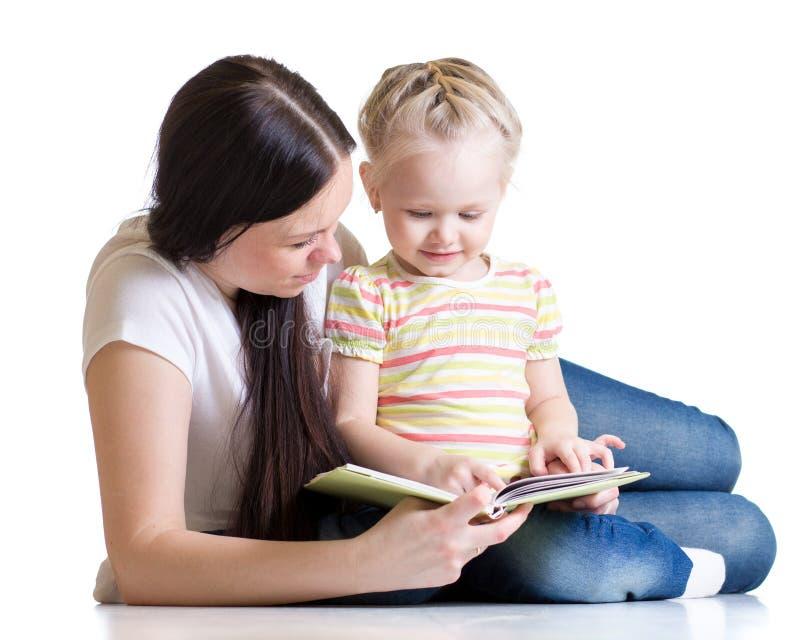 Embrome a la muchacha y su mamá leyó un libro foto de archivo libre de regalías