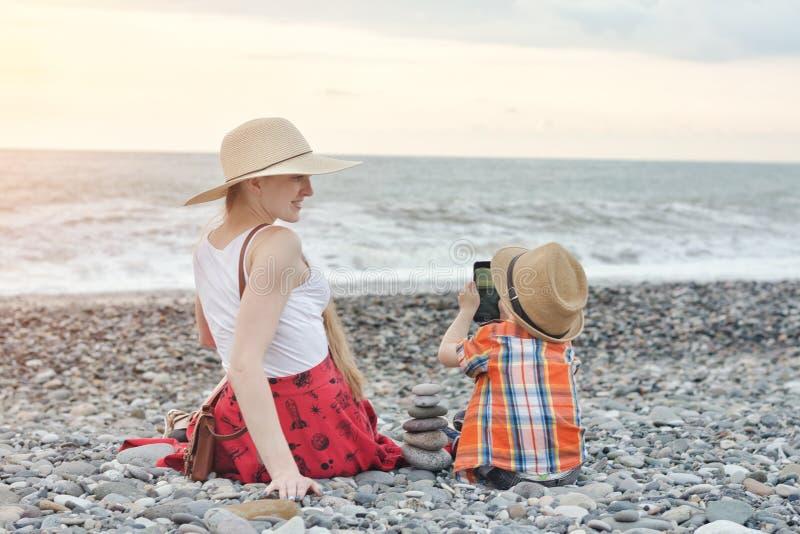 Embrome las fotografías su madre en el teléfono, costa del mar fotografía de archivo