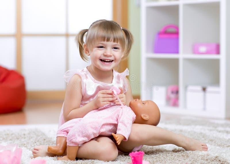 Embrome los juegos de la muchacha con la muñeca en casa en los niños foto de archivo
