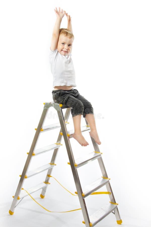 Embrome sentarse encima del stepladder, manos levantan para arriba. imagen de archivo libre de regalías