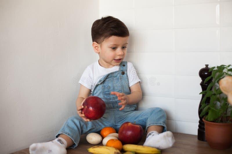 Embrome tener una tabla por completo de alimento biol?gico Ni?o alegre que come la ensalada y las frutas sanas Beb? que elige ent imagenes de archivo