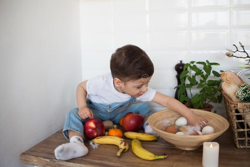 Embrome tener una tabla por completo de alimento biol?gico Ni?o alegre que come la ensalada y las frutas sanas Beb? que elige ent foto de archivo libre de regalías