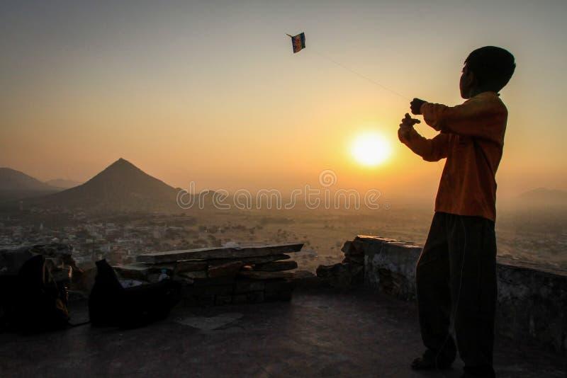 Embrome volar su cometa en la puesta del sol en Pap Mochani Gayatri Temple, Pushkar, Rajasthán, la India foto de archivo