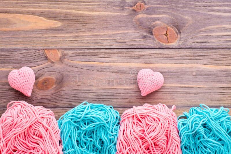 Embrouillements de fil rose et en bon état et de coeurs de tricotage photo stock