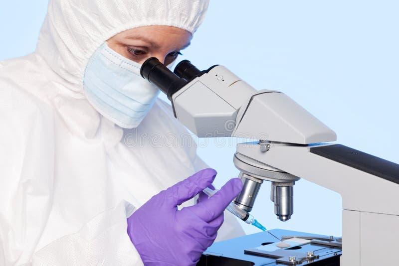 Embryologist die een steekproef haalt die een spuit gebruikt. stock fotografie