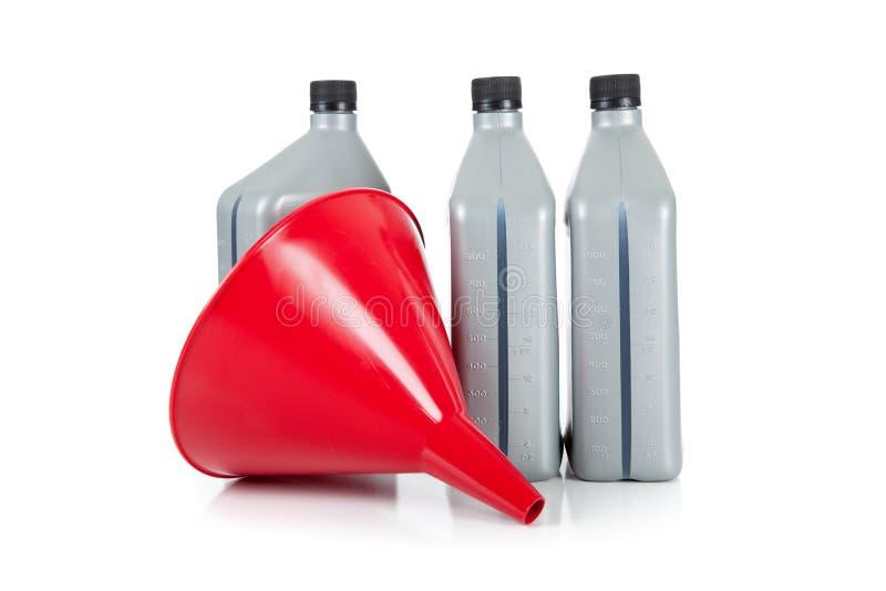 Embudo rojo y cuartos de galón de petróleo de motor en blanco imágenes de archivo libres de regalías