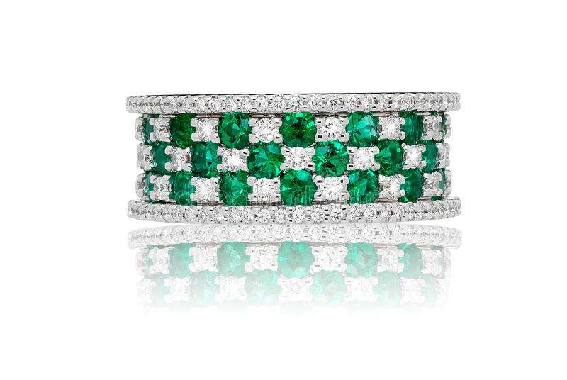 Emerald and diamond ring. With a broad band set with alternate faceted gemstones in three rows, symbolic of luxury and wealth royalty free stock image