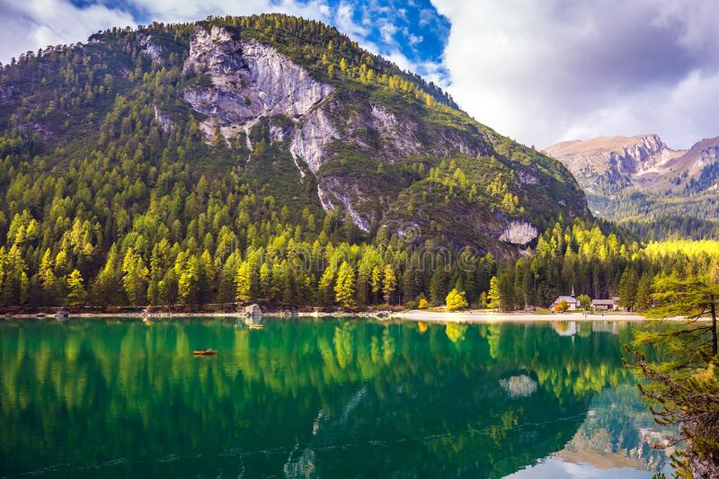 Emerald expanse of water. Magnificent lake Lago di Braies. Emerald expanse of water reflects the surrounding forest and mountains. The concept of walking and eco stock photo