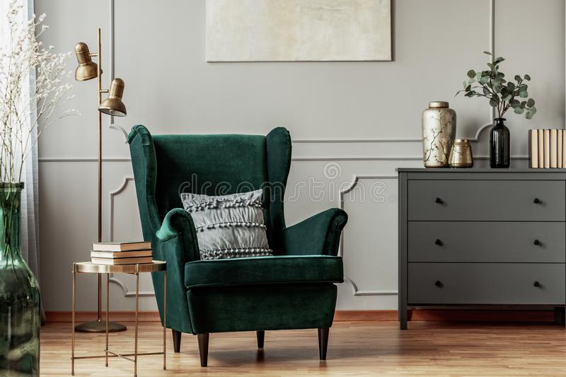 Emerald green armchair with pillow next to grey wooden commode in dark living room interior stock images