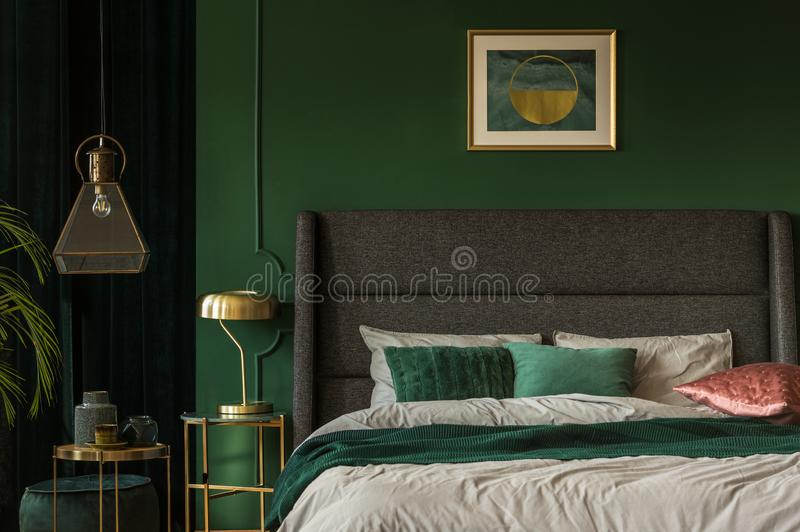 Emerald green and golden poster above comfortable king size bed with headboard and pillows in dark green bedroom. Stylish emerald green and golden poster above stock photos