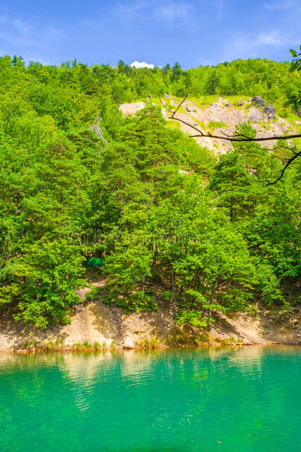 Emerald green lake color in forest. The Blue Lake from Romania change its color depending the light: from blue to emerald green. It resulted from the collapse of royalty free stock photography