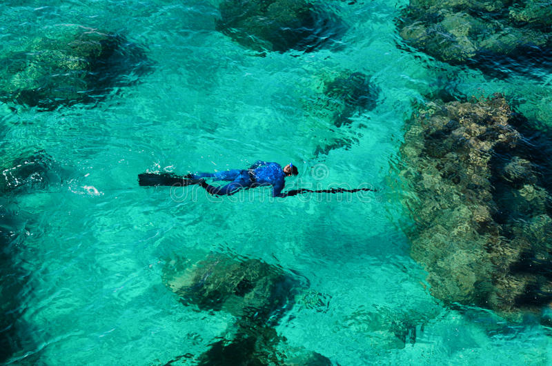 Emerald green sea water diver spearfishing. Emerald green sea water with rock and diver spearfishing royalty free stock image