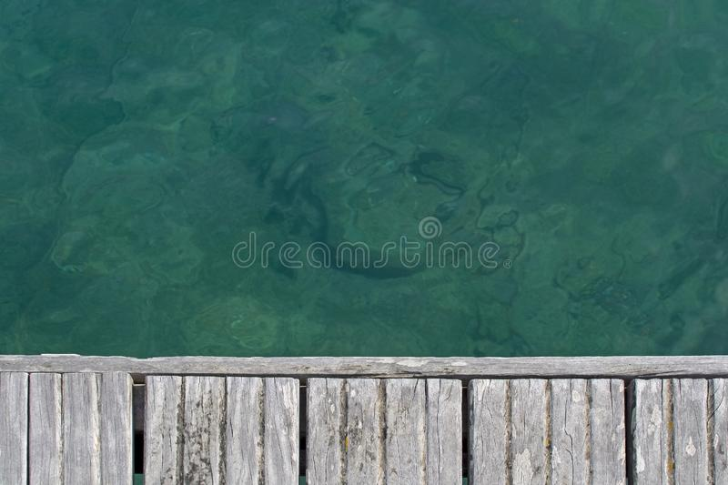 Emerald green water and wood boardwalk background texture. Sardinia, Italy stock photography