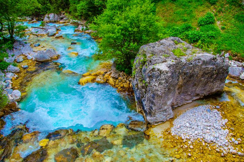 Emerald green waters fall river side bed of Soca river Isonzo between Triglav National Park Slovenia Caporetto in Italy. The emerald green waters fall river side stock photo